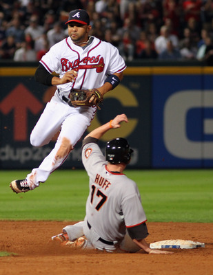 ATLANTA - OCTOBER 11:  Shortstop Alex Gonzalez #2 of the Atlanta Braves turns a double play as Aubrey Huff #17 of the San Francisco Giants approaches second during the 9th inning of Game Four of the NLDS of the 2010 MLB Playoffs on October 11, 2010  at Tu