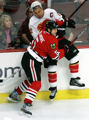 CHICAGO - MARCH 25:  Jassen Cullimore #5 of the Chicago Blackhawks checks Jarome Iginla #12 of the Calgary Flames into the boards on March 25, 2007 at the United Center in Chicago, Illinois.  (Photo by Jonathan Daniel/Getty Images)