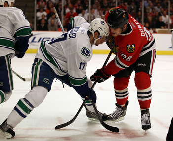 CHICAGO - OCTOBER 20: Ryan Kesler #17 of the Vancouver Canucks battles during a face-off with Jake Dowell #28 of the Chicago Blackhawks at the United Center on October 20, 2010 in Chicago, Illinois. The Blackhawks defeated the Canucks 2-1 in overtime. (Ph