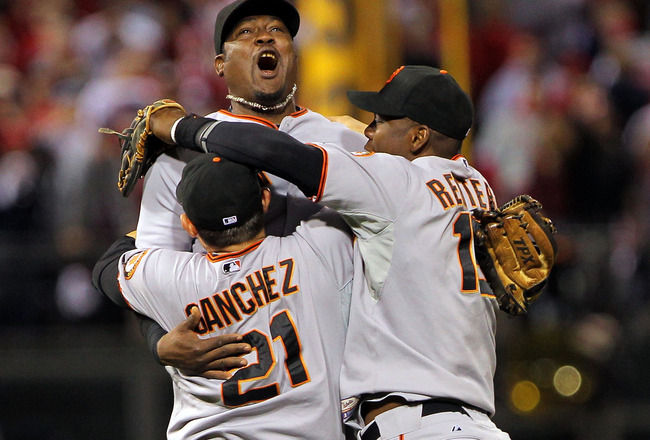 PHILADELPHIA - OCTOBER 23:  Freddy Sanchez #21, Juan Uribe #5 and Edgar Renteria #16 of the San Francisco Giants celebrate defeating the Philadelphia Phillies 3-2 and winning the pennant in Game Six of the NLCS during the 2010 MLB Playoffs at Citizens Ban