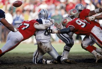 SAN FRANCISCO - JANUARY 15:  Linebacker Rickey Jackson #57 and defensive tackle Dana Stubblefield #94 of the San Francisco 49ers team up to sack Dallas Cowboys quarterback Troy Aikman #8 during the 1994 NFC Championship game at Candlestick Park on January