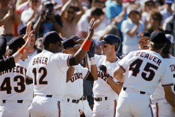 SAN FRANCISCO - OCTOBER:  Manager Dusty Baker #12 and Will Clark #22 of the San Francisco Giants high five teammates against the Chicago Cubs during the 1989 National League Championship Series at Candlestick Park in October 1989 in San Francisco, Califor