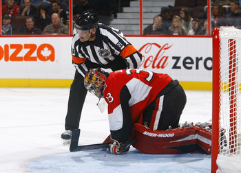 OTTAWA, ON - OCTOBER 14:  Don Van Massenhoven (21) attends to Pascal Leclaire #33 of the Ottawa Senators after suffering a groin injury during a game against the Carolina Hurricanes at Scotiabank Place on October 14, 2010 in Ottawa, Ontario, Canada.  The