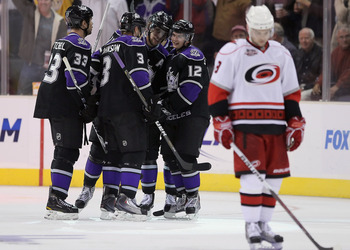LOS ANGELES, CA - OCTOBER 20:  (L-R) Willie Mitchell #33, Jack Johnson #3, Anze Kopitar #11 and Andrei Loktionov #12 of the Los Angeles Kings celebrate Loktionov's third period goal against the Carolina Hurricanes at Staples Center on October 20, 2010 in