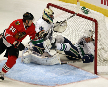 CHICAGO - OCTOBER 20: Kevin Bieksa #3 of the Vancouver Canucks falls over Roberto Luongo #1 on an interference call against Tomas Kopecky #82 of the Chicago Blackhawks at the United Center on October 20, 2010 in Chicago, Illinois. (Photo by Jonathan Danie