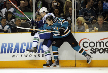 SAN JOSE, CA - SEPTEMBER 29: Torrey Mitchell #17 of the San Jose Sharks checks up against the board Keith Ballard #4 of the Vancouver Canucks during their preseason game on September 29, 2010 at the HP Pavilion in San Jose, California. The Sharks won the