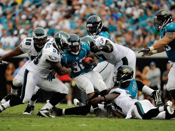 JACKSONVILLE, FL - SEPTEMBER 26:  Linebacker Trent Cole #58 and defensive tackle Brodrick Bunkley #97 of the Philadelphia Eagles bring down running back Maurice Jones-Drew #32 of the Jacksonville Jaguars at EverBank Field on September 26, 2010 in Jacksonv
