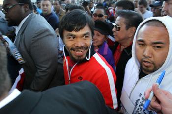 ARLINGTON, TX - MARCH 12:  (C) Manny Pacquiao of the Philippines smiles as he leaves the stage after his weigh-in for his WBO welterweight title fight against Joshua Clottey of Ghana outside Cowboys Stadium on March 12, 2010 in Arlington, Texas. Pacquiao