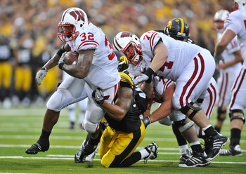 IOWA CITY, IA - OCTOBER 23: Running back John Clay #32 of the Wisconsin Badgers is tackled by line backer Lance Tillison #50 of the  University of Iowa Hawkeyes as he drove the ball up the middle of the Wisconsin Badgers during the second half of play at