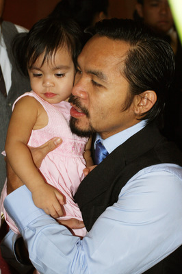 GENERAL SANTOS, PHILIPPINES - MAY 15:  World welterweight boxing champion Manny Pacquiao carries his daughter Queen  at the KCC Mall on May 15, 2010 in General Santos, Philippines. Pacquiao was there to celebrate his election on becoming a member of House