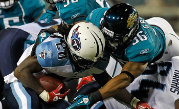 JACKSONVILLE, FL - OCTOBER 18:  Running back Chris Johnson #28 of the Tennessee Titans is tackled by safety Courtney Greene #36 of the Jacksonville Jaguars during the game at EverBank Field on October 18, 2010 in Jacksonville, Florida.  (Photo by J. Meric