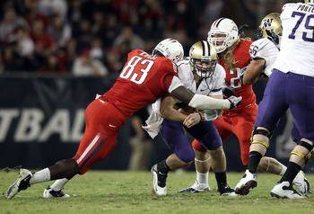 TUCSON, AZ - OCTOBER 23:  Quarterback Jake Locker #10 of the Washington Huskies is tackled by  D'Aundre Reed #83 of the Arizona Wildcats during the college football game at Arizona Stadium on October 23, 2010 in Tucson, Arizona.  (Photo by Christian Peter
