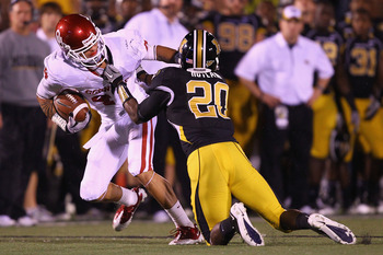 COLUMBIA, MISSOURI - OCTOBER 23: Kenny Stills #4 of the Oklahoma Sooners is tackled by Kevin Rutland #20 of the Missouri Tigers at Faurot Field/Memorial Stadium on October 23, 2010 in Columbia, Missouri.  The Tigers beat the Sooners 36-27.  (Photo by Dili