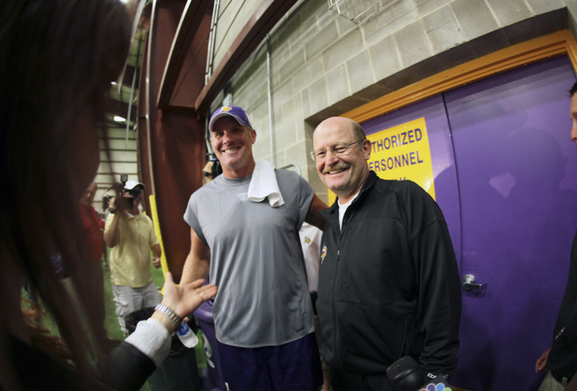 EDEN PRAIRIE, MN - AUGUST 18: Minnesota Vikings quarterback Brett Favre talks with the media as head coach Brad Childress smiles following a press conference after the first morning practice since returning to Vikings Winter Park on August 18, 2010 in Ede