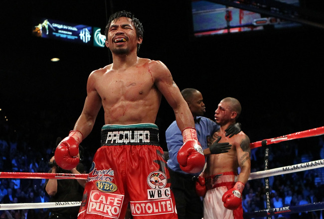 LAS VEGAS - NOVEMBER 14:  Manny Pacquiao celebrates his 12 round TKO victory against Miguel Cotto as Cotto is consoled by referee Kenny Bayless after their WBO welterweight title fight at the MGM Grand Garden Arena on November 14, 2009 in Las Vegas, Nevad