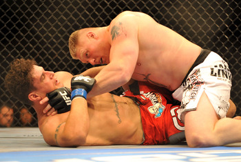 LAS VEGAS - JULY 11:  Brock Lesnar holds down Frank Mir during their heavyweight title bout during UFC 100 on July 11, 2009 in Las Vegas, Nevada.  (Photo by Jon Kopaloff/Getty Images)