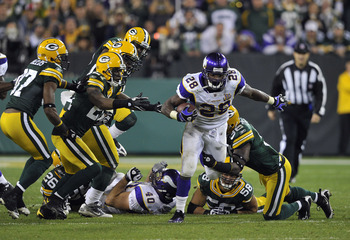 GREEN BAY, WI - OCTOBER 24:  Adrian Peterson #28 of the Minnesota Vikings breaks through the Green Bay Packers defense during their game at Lambeau Field on October 24, 2010 in Green Bay, Wisconsin. (Photo by Jim Prisching/Getty Images)