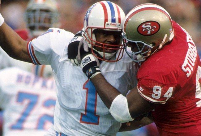 SAN FRANCISCO - DECEMBER 25:  Defensive tackle Dana Stubblefield #94 of the San Francisco 49ers attempts to sack quarterback Warren Moon #1 of the Houston Oilers during a game at Candlestick Park on December 25, 1993 in San Francisco, California.  The Oil