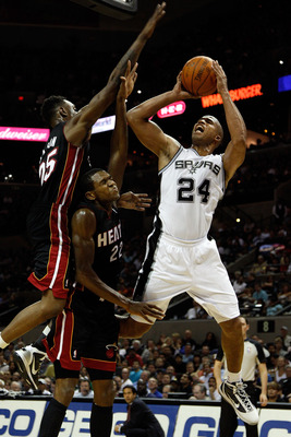 SAN ANTONIO - OCTOBER 09:  Richard Jefferson #24 of the San Antonio Spurs makes a shot over James Jones #22 and Anthony Mason #25 of the Miami Heat at the AT&T Center on October 9, 2010 in San Antonio, Texas.  NOTE TO USER: User expressly acknowledges and