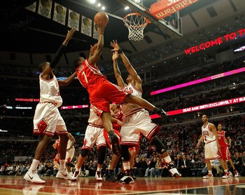 CHICAGO - MARCH 22: Kyle Lowry #7 of the Houston Rockets puts up a shot between Hakim Warrick #21 and Derrick Rose #1 of the Chicago Bulls at the United Center on March 22, 2010 in Chicago, Illinois. NOTE TO USER: User expressly acknowledges and agrees th