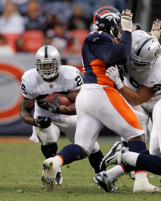 DENVER - OCTOBER 24:  Running back Michael Bush #25 of the Oakland Raiders runs through a hole in the fourth quarter against the Denver Broncos at INVESCO Field at Mile High on October 24, 2010 in Denver, Colorado. The Raiders defeated the Broncos 59-14.