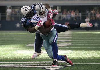 ARLINGTON, TX - OCTOBER 10:  Running back Felix Jones #28 of the Dallas Cowboys is tackled by linebacker Stephen Tulloch #55 of the Tennessee Titans at Cowboys Stadium on October 10, 2010 in Arlington, Texas. The Titans won 34-27.  (Photo by Stephen Dunn/