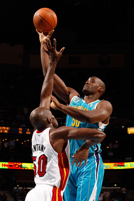 NEW ORLEANS - OCTOBER 13:  Emeka Okafor #50 of the New Orleans Hornets makes a shot over Joel Anthony #50 of the Miami Heat at the New Orleans Arena on October 13, 2010 in New Orleans, Louisiana. NOTE TO USER: User expressly acknowledges and agrees that,