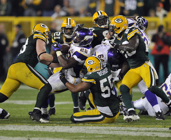 GREEN BAY, WI - OCTOBER 24:  Adrian Peterson #28 of the Minnesota Vikings is stopped by Desmond Bishop #55 of the Green Bay Packers at Lambeau Field on October 24, 2010 in Green Bay, Wisconsin. (Photo by Jim Prisching/Getty Images)