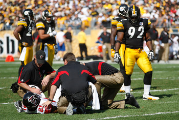 PITTSBURGH - SEPTEMBER 12:  Christopher Owens #21 of the Atlanta Falcons gets checked out by trainers while James Harrison #92 of the Pittsburgh Steelers looks on during the NFL season opener game on September 12, 2010 at Heinz Field in Pittsburgh, Pennsy