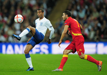 LONDON, ENGLAND - OCTOBER 12: Ashley Cole of England and Simon Vukcevic of Montenegro during the UEFA EURO 2012 Group G Qualifying match between England and Montenegro at Wembley Stadium on October 12, 2010 in London, England.  (Photo by Shaun Botterill/G