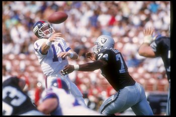 4 Oct 1992:  Quarterback Phil Simms of the New York Giants (left) passes the ball during a game against the Los Angeles Raiders at the Los Angeles Memorial Coliseum in Los Angeles, California.  The Raiders won the game, 13-10. Mandatory Credit: Stephen Du