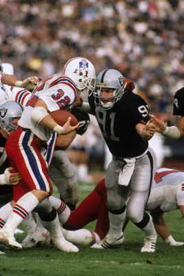 LOS ANGELES - JANUARY 5:  Linebacker Brad Van Pelt #91 of the Los Angeles Raiders closes in for a tackle on running back Craig James #32 of the New England Patriots during the 1985 AFC Divisional Playoff game at the Los Angeles Memorial Coliseum on Januar