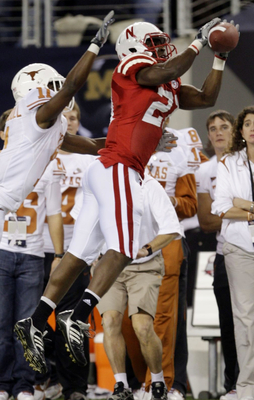 ARLINGTON, TX - DECEMBER 5:  Prince Amukamara #21 of the Nebraska Cornhuskers catches the ball for an interception in the first quarter in front of James Kirkendoll #11 of the Texas Longhorns at Cowboys Stadium on December 5, 2009 in Arlington, Texas. (Ph