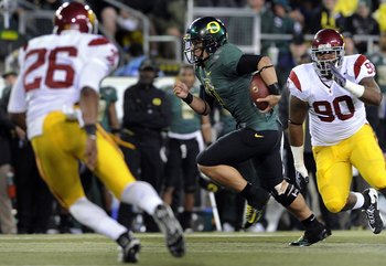 EUGENE, OR - OCTOBER 31: Quarterback Jeremiah Masoli #8 of the Oregon Ducks tucks the ball and heads upfield as safety Will Harris #26 and defensive tackle Derek Simmons #90 of the USC Trojans give chase in the second quarter of the game at Autzen Stadium