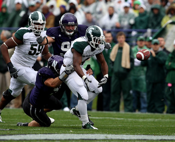 EVANSTON, IL - OCTOBER 23: Edwin Baker #4 of the Michigan State Spartans fumbles the ball as he is hit by Bryce McNaul #51 and Tyler Scott #97 of the Northwestern Wildcats at Ryan Field on October 23, 2010 in Evanston, Illinois. Michigan State defeated No
