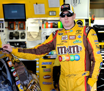 MARTINSVILLE, VA - OCTOBER 22:  Kyle Busch, driver of the #18 M&M's Toyota, stands in the garage prior to practice for the NASCAR Sprint Cup Series TUMS Fast Relief 500 at Martinsville Speedway on October 22, 2010 in Martinsville, Virginia.  (Photo by Rus