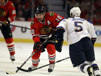 CHICAGO - OCTOBER 18: Patrick Sharp #10 of the Chicago Blackhawks looks to pass against Barret Jackman #5 of the St. Louis Blues at the United Center on October 18, 2010 in Chicago, Illinois. The Blackhawks defeated the Blues 3-2 in overtime.  (Photo by J