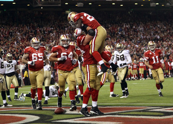 SAN FRANCISCO - SEPTEMBER 20:  Joe Staley #74 lifts up Anthony Dixon #24 of the San Francisco 49ers after Dixon scored a touchdown against the New Orleans Saints at Candlestick Park on September 20, 2010 in San Francisco, California.  (Photo by Ezra Shaw/