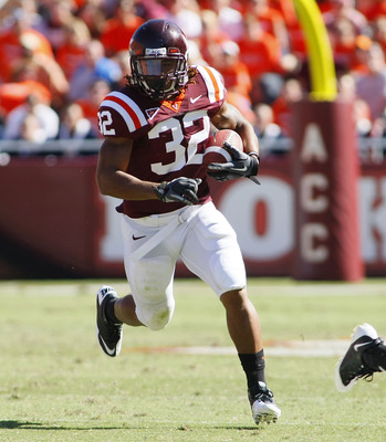 BLACKSBURG, VA - SEPTEMBER 18: Running back Darren Evans #32 of the Virginia Tech Hokies runs with the ball as cornerback Travis Simmons #13 of the East Carolina Pirates defends at Lane Stadium on September 18, 2010 in Blacksburg, Virginia.  (Photo by Geo