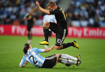 CAPE TOWN, SOUTH AFRICA - JULY 03:  Lukas Podolski of Germany jumps over the challenge of Martin Demichelis of Argentina during the 2010 FIFA World Cup South Africa Quarter Final match between Argentina and Germany at Green Point Stadium on July 3, 2010 i
