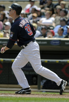 MINNEAPOLIS, MN - JUNE 30: Justin Morneau #33 of the Minnesota Twins watches the flight of his solo home run in the sixth inning against the Detroit Tigers during their game on June 30, 2010 at Target Field in Minneapolis, Minnesota. (Photo by Hannah Fosl