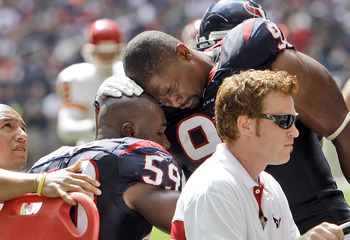 HOUSTON - OCTOBER 17:  DeMeco Ryans #59 of the Houston Texans is comforted by  Amobi Akoye #91 as he is carted off the field at Reliant Stadium on October 17, 2010 in Houston, Texas.  (Photo by Bob Levey/Getty Images)