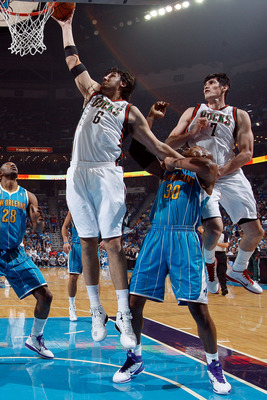 NEW ORLEANS - OCTOBER 27:  Andrew Bogut #6 of the Milwaukee Bucks shoots the ball over Emeka Okafor #50 of the New Orleans Hornets at the New Orleans Arena on October 27, 2010 in New Orleans, Louisiana.   The Hornets defeated the Bucks 95-91.   NOTE TO US