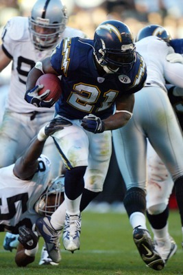 SAN DIEGO - DECEMBER 28:  Runningback LaDainian Tomlinson #21 of the San Diego Chargers runs through the defense of the Oakland Raiders in the 2nd half  during their NFL  game on December 28, 2003 at Qualcomm Stadium in San Diego, California. Tomlinson be