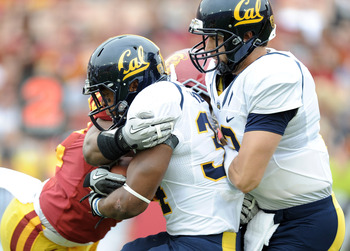 LOS ANGELES, CA - OCTOBER 16:  Shane Vereen #34 of the California Golden Bears is knocked back into Kevin Riley #13 for a loss by Hunter Simmons #48 of the USC Trojans during the first quarter at Los Angeles Memorial Coliseum on October 16, 2010 in Los An