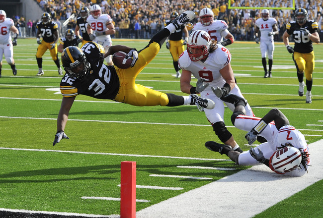 IOWA CITY, IA - OCTOBER 23- Running back Adam Robinson #32 of the University of Iowa Hawkeyes is knocked down at the one yard line by line backer Blake Sorensen #9 of the Wisconsin Badgers during the first half of play at Kinnick Stadium on October 23, 20