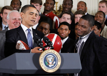 WASHINGTON - MARCH 08:  U.S. President Barack Obama (L) receives a football helmet during an East Room event to host members of the Alabama Crimson Tide March 8, 2010 at the White House in Washington, DC. Obama welcomed the 2009 BCS Champion to honor its