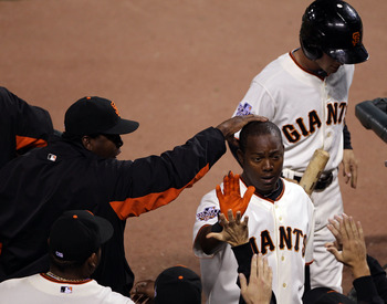 SAN FRANCISCO - OCTOBER 28:  (R) Edgar Renteria #16 of the San Francisco Giants is greeted by teammates in the dugout after scoring a run in the eighth inning taking on the Texas Rangers in Game Two of the 2010 MLB World Series at AT&T Park on October 28,