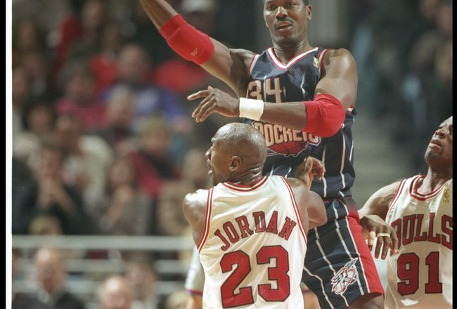 11 Jan 1997:  Center Hakeem Olajuwon of the Houston Rockets leaps for control of the balll over the defense of guard Michael Jordan (center)  and forward Dennis Rodman of the Chicago Bulls during a game at the United Center in Chicago, Illinois.  The Bull