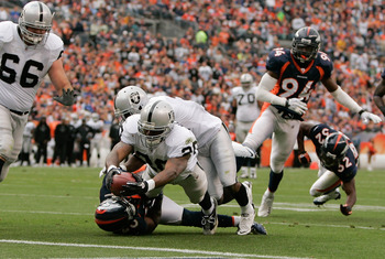 DENVER - OCTOBER 24:  Running back Darren McFadden #20 of the Oakland Raiders stretches the ball across the goal line for a touchdown in the second quarter against the Denver Broncos at INVESCO Field at Mile High on October 24, 2010 in Denver, Colorado. (
